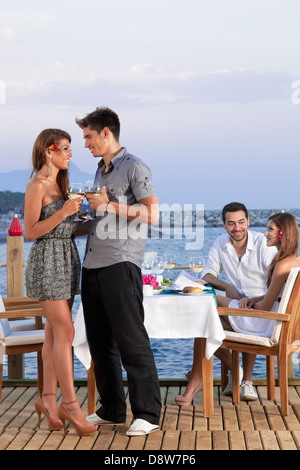 Young romantic couple standing close together on a wooden deck overlooking the sea drinking white wine. - Stock Photo