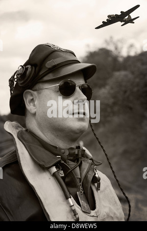 A sepia toned monochrome image of a reenactor dressed as a WW2 bomber pilot looking skyward as a B17 Flying Fortress - Stock Photo