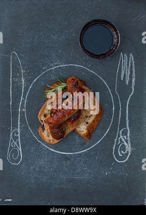 Bread with grilled sausages and a glass of wine; Plate,knife and fork drawn on the table - Stock Photo