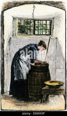 Woman bending over a churn to gather butter. Hand-colored woodcut - Stock Photo