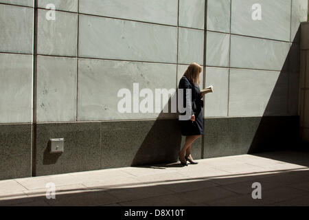 London, UK. 5th June 2013. Office workers in Canary Wharf enjoy the warm sunshine during their lunch break as temperatures - Stock Photo