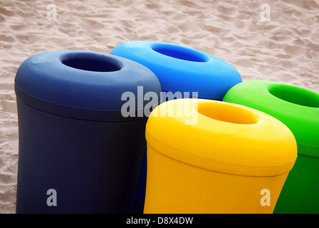 Green blue yellow and black recycling materials baskets in a beach - Stock Photo