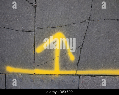 yellow painted arrow on grey pavement - Stock Photo
