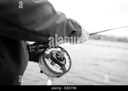 Male holding fishing fly rod and reel on the Upper Clark Fork River near Missoula, Montana - Stock Photo