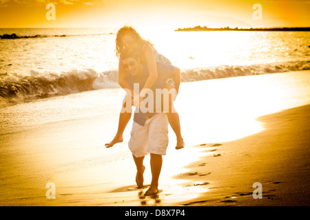 Young couple on the beach playing at the shoreline he carrys her piggy back style - Stock Photo