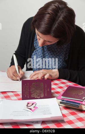 Woman filling out a passport renewal application - Stock Photo