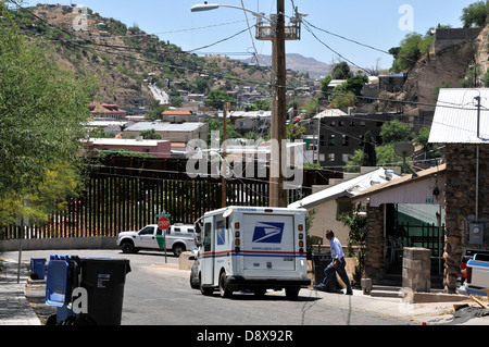 A US postal worker delivers mail to a residence near the border wall in Nogales, Arizona, USA, across from Sonora, - Stock Photo