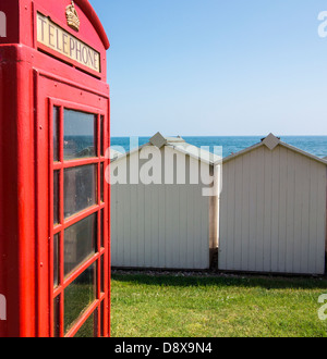Old red telephone box and beach huts on the seafront at Budleigh Salterton, Devon, England - Stock Photo