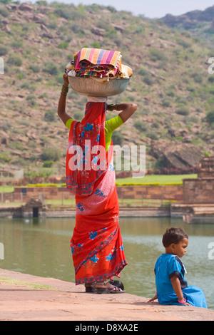 Asia, India, Karnataka, Badami, Agastya lake, Indian woman carries washed clothes on her head - Stock Photo