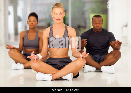 group of young fit people meditating in a gym class - Stock Photo