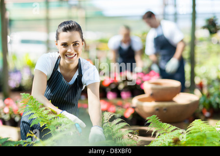 happy female nursery worker trimming plants in greenhouse - Stock Photo