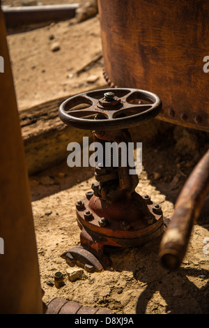 Rusty, half-buried valve assembly attached to settling tanks at a historic mining property at a mine in the Mojave - Stock Photo
