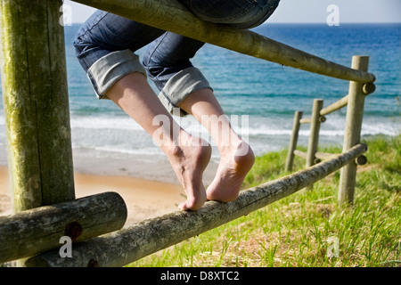 Legs of a young woman resting on a wooden fence near the beach - Stock Photo
