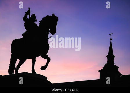 Spain, Madrid, Equestrian statue of King Philip II in Plaza Mayor silhouetted against evening sky. - Stock Photo