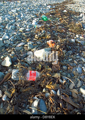 Plastic bottles and other refuse caught up in the seaweed on an Irish Beach - Stock Photo
