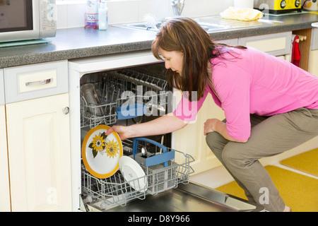 woman loading the dishwasher - Stock Photo