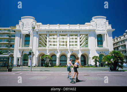Roller bladers  passing  the Palais de la Mediterranee hotel on the Promenade des Anglais, Nice, Cote d'Azur, Riviera, - Stock Photo