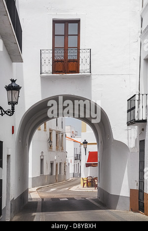 Spain, Extremadura, Olivenza, Archway in typically narrow empty street with whitewashed buildings. - Stock Photo