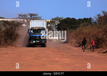Gambia heavy goods vehicle carrying sea container on unsurfaced red dirt road to terminal on the Bund Road - Stock Photo