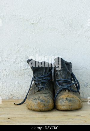 A pair of Steel Toe Work Boots with dry mud against a white wall. - Stock Photo
