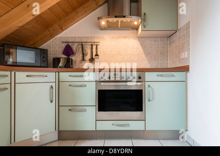 kitchen of a flat with oven, microwave, stove, hood, cabinets and wooden ceiling - Stock Photo