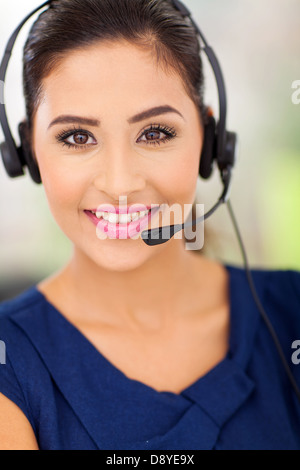 Closeup portrait of a happy young call center employee smiling with a headset - Stock Photo