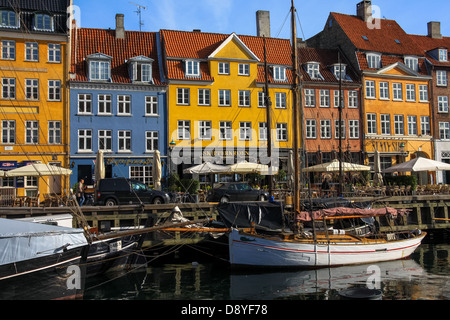 Houses along waterfront and wooden ships in Nyhavn harbor, Copenhagen, Denmark - Stock Photo