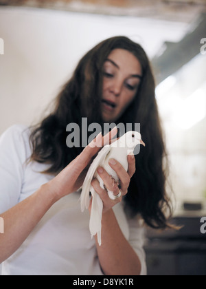 A woman holding a white dove, Skane, Sweden. - Stock Photo