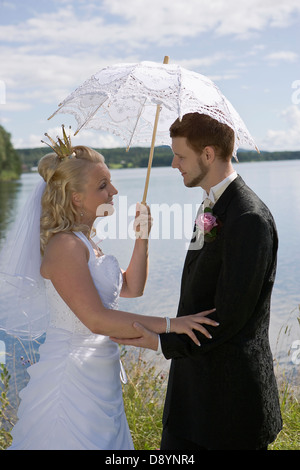 Bride and groom standing by lake with holding umbrella, side view - Stock Photo