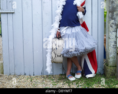 A girl dressed in a range of costumed items and props. - Stock Photo