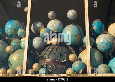 Netherlands, Amsterdam, World globes jumbled in shop window - Stock Photo
