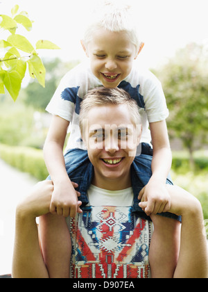 Teenage boy carrying younger brother on shoulders - Stock Photo