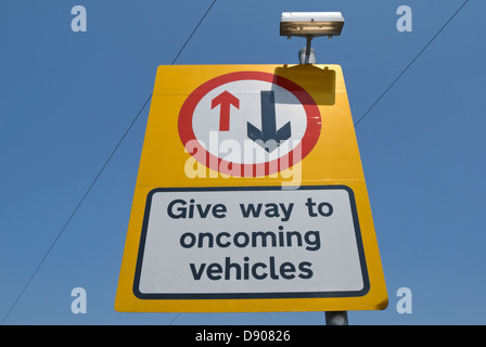 british road sign instructing drivers to give way to oncoming vehicles - Stock Photo