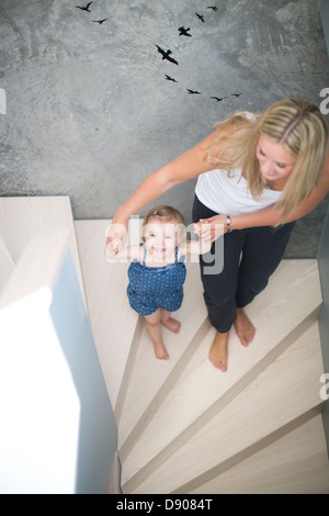 Mother and daughter walking on steps - Stock Photo