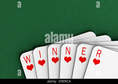 Playing cards on a felt table spelling out the word winner - Stock Photo