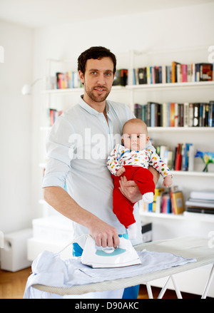 Father holding baby and ironing - Stock Photo