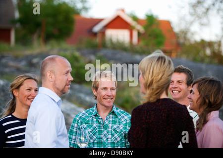 Six adults spending time together, Fejan, Stockholm archipelago, Sweden.