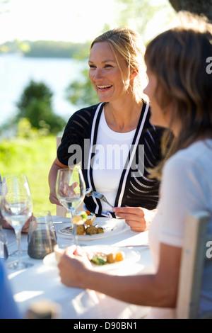 Two women having lunch at a midsummer party, Fejan, Stockholm archipelago, Sweden.