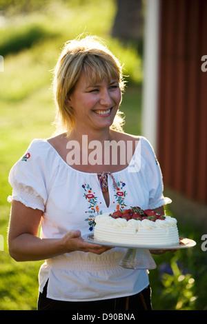 A woman and a strawberry cake, Fejan, Stockholm archipelago, Sweden.