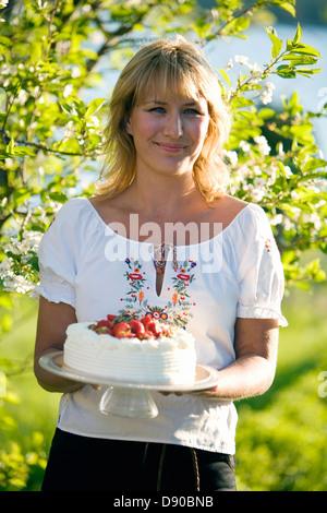 Woman with a strawberry cake, Fejan, Stockholm archipelago, Sweden.