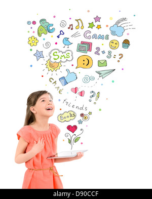Happy cute little girl in red dress holding a digital tablet in hand and looking up at the colorful icons of entertainment - Stock Photo