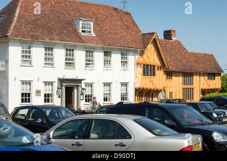 Cars parked in the Market Square, Levanham, in front of historic buildings. - Stock Photo