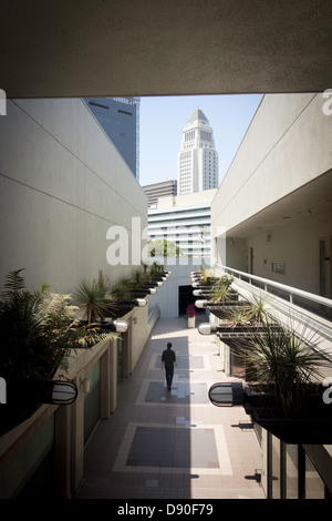 Man walks down pedestrian alley in downtown Little Tokyo near Los Angeles City Hall Civic Center building in LA - Stock Photo