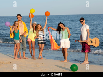 Group of young people enjoying beach party with guitar and balloons. - Stock Photo