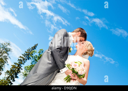 Low-angle view of groom and bride embracing outdoors - Stock Photo