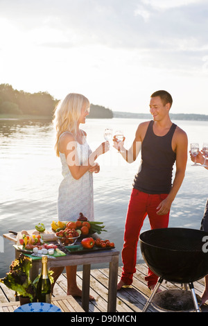 Couple standing on jetty toasting with glasses - Stock Photo