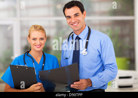 portrait of medical doctor and young female nurse in office - Stock Photo