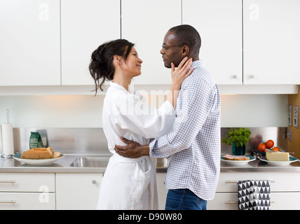 Smiling couple embracing in kitchen - Stock Photo