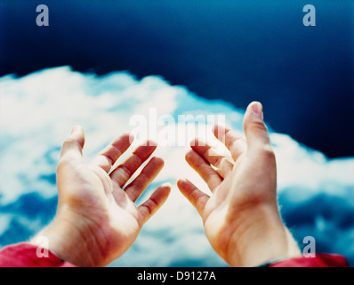 Hands reaching towards the sky. - Stock Photo