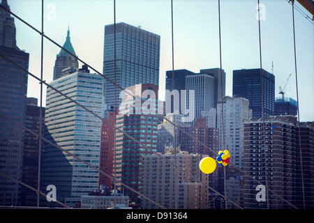 Colorful balloons on Brooklyn Bridge with skyscrapers in background - Stock Photo